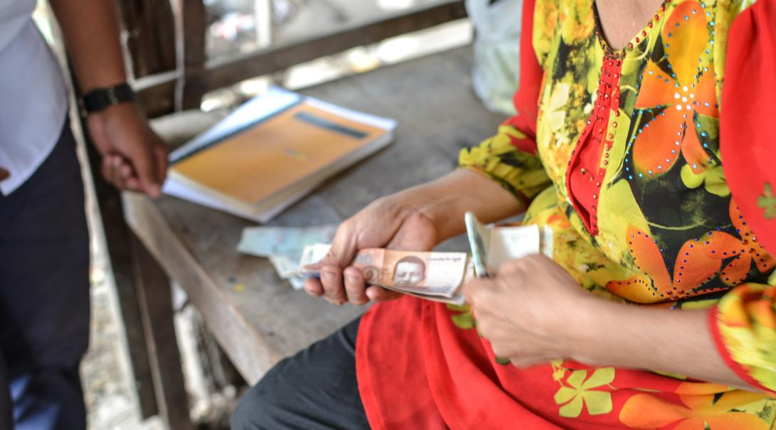 Beneficiary pays back her loan during the Micro-finance internship in Cambodia.